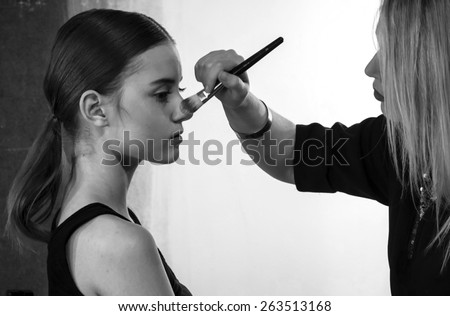 KIEV, UKRAINE - MARCH 18, 2015: A model has her makeup done backstage during Ukrainian Fashion Week - stock photo