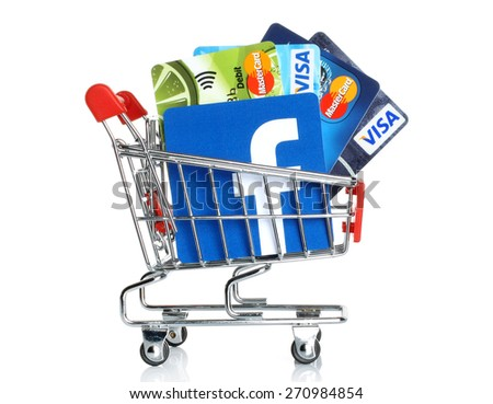 KIEV, UKRAINE - MARCH 21, 2015: Facebook logo printed on paper and placed into shopping cart with cards Visa and MasterCard on white background.New Facebook payment concept. - stock photo