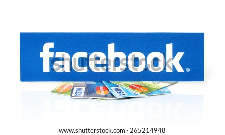KIEV, UKRAINE - MARCH 21, 2015: Facebook logo printed on paper and placed on cards Visa and MasterCard on white background.New Facebook payment concept. - stock photo