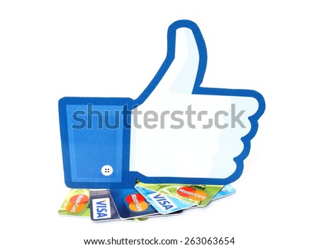 KIEV, UKRAINE - MARCH 21, 2015: Facebook thumbs up sign printed on paper and placed on cards Visa and MasterCard on white background.New Facebook payment concept. - stock photo