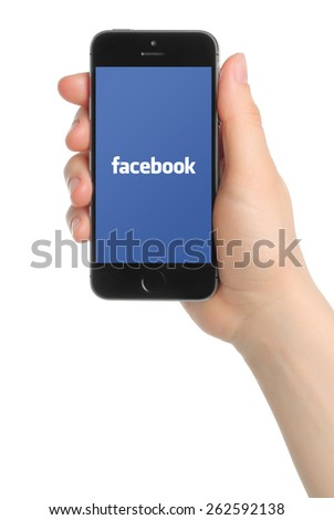 KIEV, UKRAINE - MARCH 7, 2015:Hand holds iPhone 5s Space Gray with Facebook logo on white background. Facebook is a well-known social networking service. - stock photo