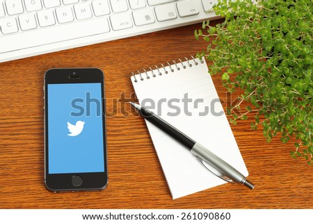 KIEV, UKRAINE - MARCH 7, 2015:iPhone with Twitter logotype on its screen and keyboard, notepad, pen, green plant on wooden background - stock photo