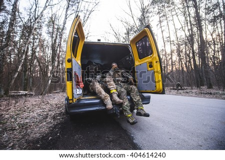 """KIEV,UKRAINE - March 26:Soldiers with weapon in truck with open doors on forest road during military training """"RUH 100.Tryzub"""" for civilians in Kiev,Ukraine on March 26,2016. - stock photo"""