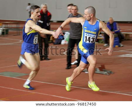 KIEV, UKRAINE - MARCH 03: Unidentified men at the relay race on Ukrainian Veteran Track & Field Championships on March 03, 2012 in Kiev, Ukraine. - stock photo