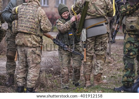 "KIEV,UKRAINE - March 26 : Woman with weapon helps to tie yellow tape-marker to man in uniform during military training for civilians ""RUH 100.Tryzub"" in Kiev,Ukraine on March 26,2016."