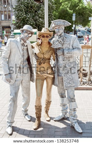 KIEV, UKRAINE - MAY 09: A company of unidentified busking mimes perform on Khreshchatyk street in Kiev, Ukraine on May 09, 2013. Living statues are the entertainment for the tourists. - stock photo