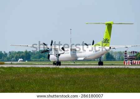 KIEV, UKRAINE - MAY 20, 2015:  Air Baltic propeller airplane landed and taxiing to teminal at International Borispol airport on May 20, 2015. Airbaltic is Latvian national airline