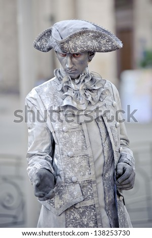 KIEV, UKRAINE - MAY 11: An unidentified busking mime in a costume of 18th century with tricorne performs on Khreshchatyk street in Kiev, Ukraine on May 11, 2013. Living statues entertain the tourists. - stock photo