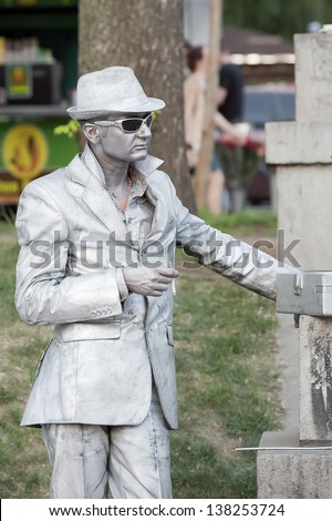 KIEV, UKRAINE - MAY 11: An unidentified busking mime with a cigarette performs on Khreshchatyk street in Kiev, Ukraine on May 11, 2013. Living statues are the entertainment for the tourists. - stock photo