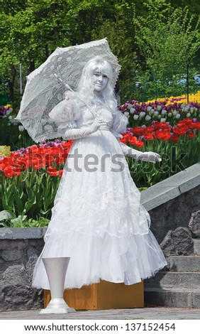 KIEV, UKRAINE - MAY 01: An unidentified busking mime with parasol performs in Spivoche Pole park in Kiev, Ukraine on May 01, 2013. Living statue is the usual entertainment for the tourists. - stock photo