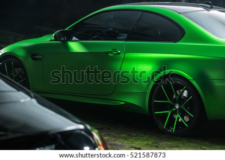 Kiev, Ukraine - 14 May 2014: BMW M3 Coupe tuning sport-car. It colored in acid green color. Editorial photo. Shoot from the side.