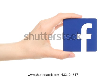 Kiev, Ukraine - May 18, 2016: Hand holds facebook logo printed on paper on white background. Facebook is a well-known social networking service.