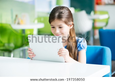 KIEV, UKRAINE - MAY 21, 2014: Little smiling  girl sitting at the desk and looking on a brand new Apple iPad Air. Apple iPad Air developed by Apple inc. and was released on November 1, 2013. - stock photo