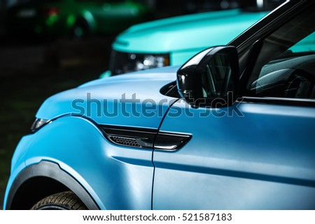 Kiev, Ukraine - 14 May 2014: Range Rover EVOQUE tuning sport-car. It colored in cyan and black colors. Editorial photo. Closeup side view.