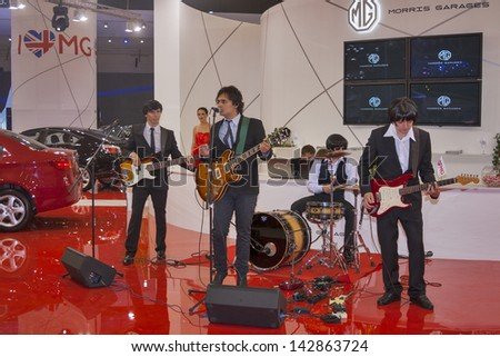 KIEV, UKRAINE - MAY 29: Unknown rock band simulates The Beatles at Morris Garages presentation at SIA' 2013 International Motor Show in International Exhibition Centre on May 29, 2013 in Kiev, Ukraine - stock photo