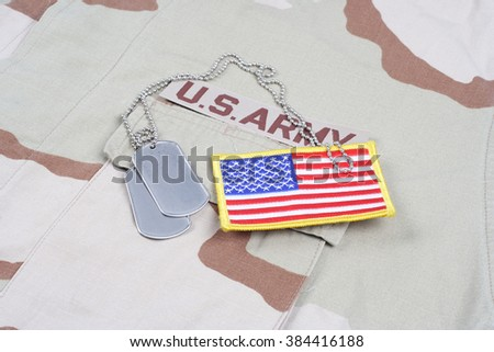 KIEV, UKRAINE - May 9, 2015. US ARMY branch tape with dog tags on desert camouflage uniform background