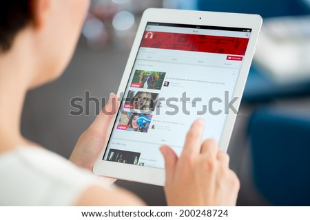 KIEV, UKRAINE - MAY 21, 2014: Woman holding a brand new Apple iPad Air and looking on YouTube music playlist on a screen. YouTube is the popular video-sharing website that founded in February 14, 2005 - stock photo