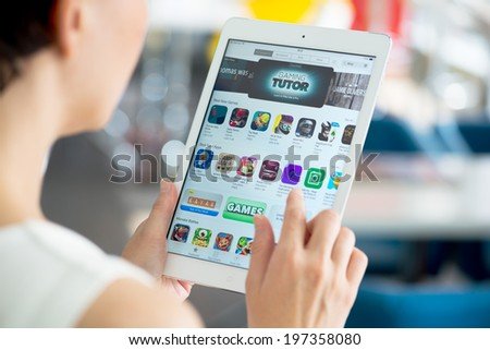 KIEV, UKRAINE - MAY 21, 2014: Woman looking for a new game apps using App Store on brand new Apple iPad Air. Apple iPad Air is developed by Apple inc. and was released on November 1, 2013. - stock photo