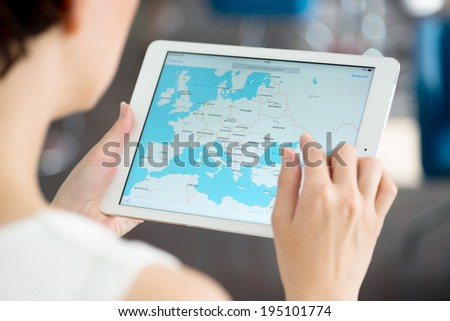 KIEV, UKRAINE - MAY 21, 2014: Woman looking on Google Maps application on a brand new white Apple iPad Air. Google Maps is a most popular web mapping service for mobile provided by Google inc. - stock photo