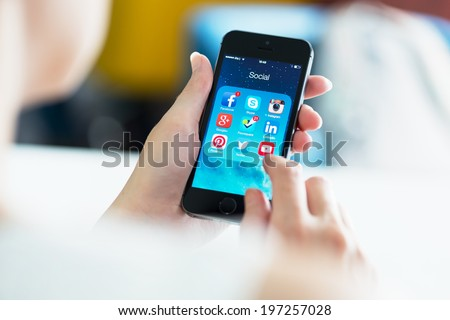 KIEV, UKRAINE - MAY 21, 2014: Woman looking on social media applications on a brand new black Apple iPhone 5S, which is designed and developed by Apple inc. and was released on September 20, 2013. - stock photo
