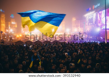 Kiev, Ukraine - 24 November, 2013: Meeting on the Independence square at night in Kiev. Girl holding a flag of Ukraine. During revolution to support the integration of Ukraine into the European Union. - stock photo