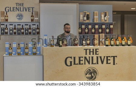 KIEV, UKRAINE - NOVEMBER 21, 2015: Unrecognized presenter works on The Glenlivet Single Malt Scotch Whisky Highland distillery booth at 1st Ukrainian Whisky Dram Festival in Parkovy Exhibition Center. - stock photo