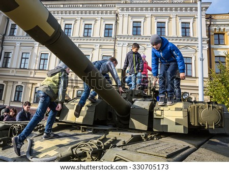 "KIEV, UKRAINE - Oct 17, 2015: Exhibition of military equipment ""Power of Unbroken"" on the occasion of the Day of Defender of Ukrain. Children are considering military equipment"