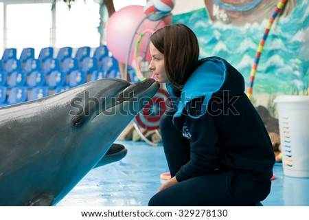 KIEV, UKRAINE - OCTOBER 10: A dolphin kisses an unidentified girl, the coach, at the dolphin assisted therapy session on October 10, 2015 in Kiev, Ukraine - stock photo