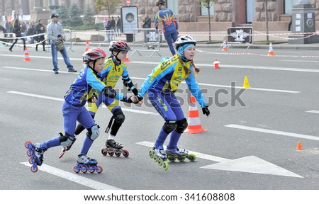 KIEV, UKRAINE - OCTOBER 21, 2012: Town sport competition between schoolchildren, the race on roller skates. Heat of three little schoolchildren.
