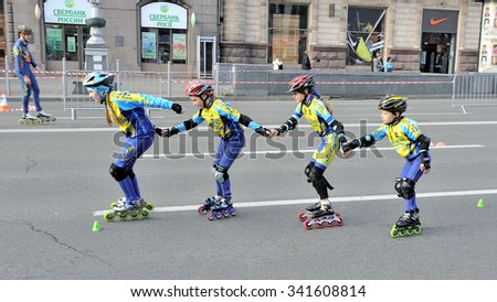 KIEV, UKRAINE - OCTOBER 21, 2012: Town sport competition between schoolchildren, the race on roller skates. Heat of four little schoolchildren.