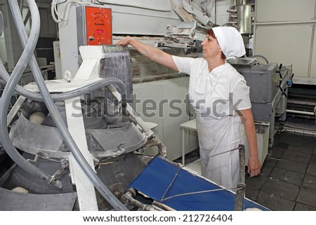 KIEV, UKRAINE - on August 21, 2014: the worker of the Kiev grain plant, moves ready dough to the container - stock photo