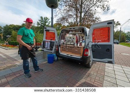 KIEV, UKRAINE - 16 SEP, 2013: Mobile coffee cafe in the city center with one, smiling, man, serving coffee from the back of his van.