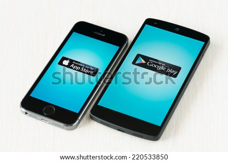 Kiev, Ukraine - September 29, 2014: Close-up shot of brand new Apple iPhone 5S and Google Nexus 5 smartphones with App Store and Google Play logos on a screen. - stock photo