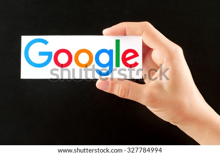 Kiev, Ukraine - September 02, 2015:Hand holds new Google logotype printed on paper on blackboard background.Google is USA multinational corporation.
