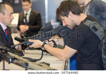 "Kiev, Ukraine - September 22, 2015: MMan studying a sample of the automatic rifle at the specialized exhibition ""Arms and Security - 2015"""