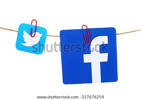 KIEV, UKRAINE - SEPTEMBER 05, 2015: Popular social media Facebook, Twitter hanging on the clothesline isolated on white background. - stock photo