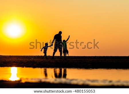 Kijkduin beach, the Netherlands - September 07, 2016: father and children on the beach during warmest September in 100 years