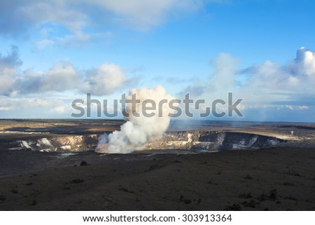 Kilauea volcano exploding after an earthquake spills rocks into the molten lava of the active vent within the caldera. - stock photo