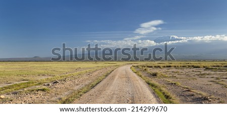 Kilimanjaro with snow cap seen from Amboseli National Park in Kenya with a road in the foreground. - stock photo