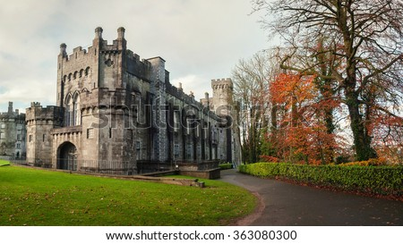 Kilkenny Castle and gardens in autumn with heavy clouds. It is one of the most visited tourist sites in Ireland - stock photo