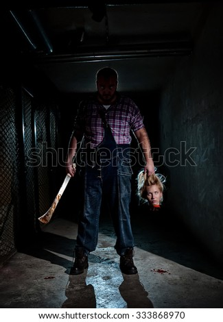 Killer and the victim on Halloween night, dark basement, women beheaded by the forester wit an axe - stock photo