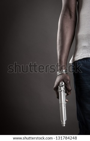 Killer with gun close up over dark background with copyspace. - stock photo