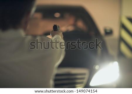 Killer with gun. Rear view of men with handgun aiming the car driver - stock photo
