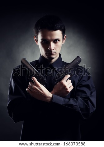 Killer with two pistols on dark background - stock photo