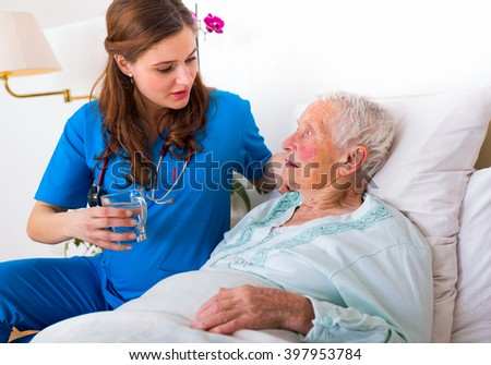 Kind caregiver bringing water to the thirsty sick elderly woman in bed.