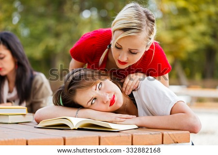 Kind classmate waking up tired student to get back and study. - stock photo