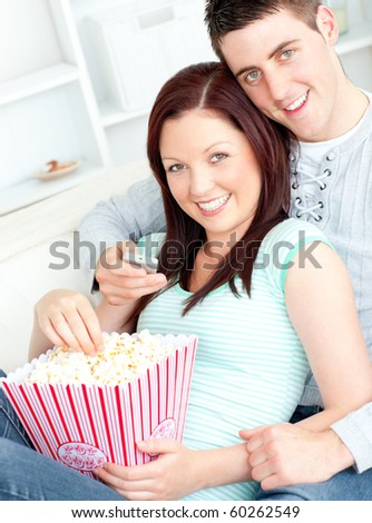 Kind couple eating popcorn and watching television lying on the sofa at home