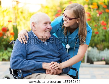 Kind doctor taking care of an old man in wheelchair. - stock photo