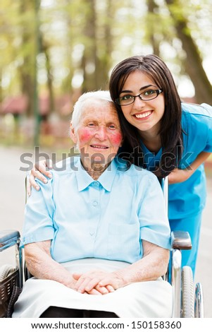 Kind elderly lady in wheelchair with a nice nurse next to her out in park. - stock photo