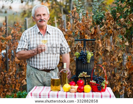 Kind elderly man smiling to the camera with a glass of wine in his hand next to autumn crops. - stock photo